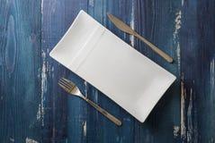 Weiße rechteckige Platte mit Gabel und Messer auf blauem hölzernem backg Stockbilder