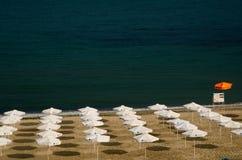 Weiße Regenschirme auf dem Strand Stockfoto