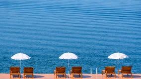 Weiße Regenschirme und Holzstühle auf hölzernem Boden über dem allgemeinen See Lizenzfreie Stockfotos
