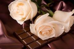 Weiße Rosen auf brauner Seide und Schokolade Lizenzfreie Stockfotos