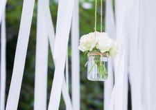 Weiße Rosen in einem GlasVase mit weißen Farbbändern Stockfotografie