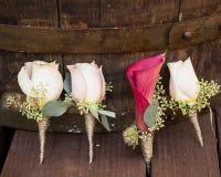 Weiße Rosen Groomsmen Boutonniere und hölzerner Hintergrund der Rosabräutigamlilie Lizenzfreies Stockfoto