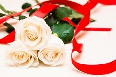 Weiße Rosen mit rotem Band auf einem hellen hölzernen Hintergrund Women Stockfotografie