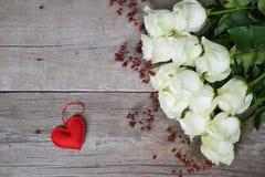 Weiße Rosen mit rotem Herzen und Hagebutten auf hölzernem Hintergrund Lizenzfreie Stockbilder