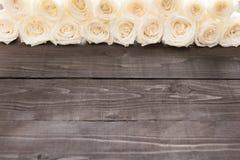 Weiße Rosen sind auf dem hölzernen Hintergrund Lizenzfreie Stockfotos