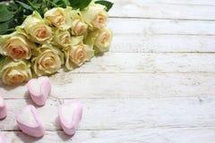 Weiße Rosen und Herzen eines Eibisches auf einem weißen hölzernen Hintergrund stockfotografie