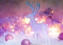 Weiße Rotwildfigürchen mit hellen roten Bällen gegen Lichter der Girlande Gemütliche nordische Häuschenart des skandinavischen La Lizenzfreie Stockfotos