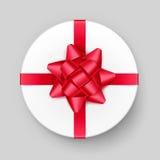 Weiße runde Geschenkbox mit rotem Bogen und Band Stockbild