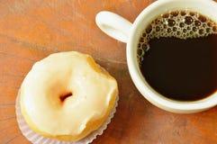 weiße Sahneschaumgummiringe und schwarze Kaffeetasse auf hölzernem Brett Stockbild