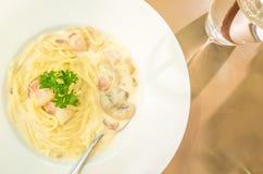 Weiße sahnige Soße der Spaghettis mit Schinken und Pilz auf Weiß flechten Stockfoto