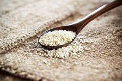 Weiße Samen des indischen Sesams in einem hölzernen Löffel auf einer Leinentischdecke Stockfotografie