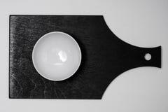 Weiße Schüssel auf schwarzem Brett lizenzfreies stockbild