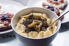 Weiße Schüssel Corn-Flakes und Scheibe der Banane Stockfotografie