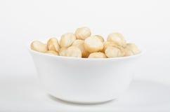 Weiße Schüssel gefüllt mit gebratenen Macadamiamuttern Stockbilder