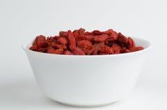 Weiße Schüssel gefüllt mit getrockneten roten wolfberries Stockbild