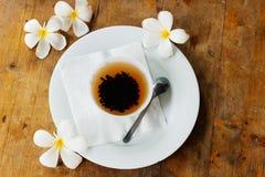 Weiße Schale Ceylon-Tee und gelber exotischer Blumen Plumeria - flacher Lage Sri Lanka-` s Hintergrund mit hölzerner alter Tabell stockbild