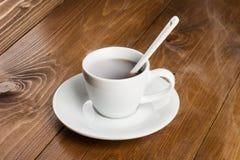 Weiße Schale dampfiger Kaffee auf Holztisch Stockfotografie