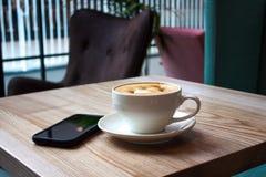 Weiße Schale des Cappuccinos und des schwarzen Handys lizenzfreie stockfotos