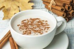 Weiße Schale des milchigen heißen Getränks der Salepwurzel von der Türkei mit Zimtpulver und Stöcke gesunder Gewürz und Herbstwin stockfoto