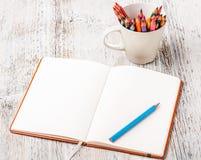 Bunte Bleistifte und Notizbuch Lizenzfreie Stockfotografie