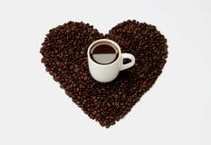 Weiße Schale mit dem Kaffee, der auf Herzen von Kaffeebohnen steht Lizenzfreies Stockfoto