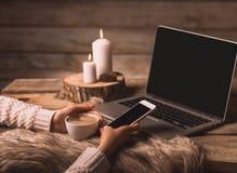 Weiße Schale mit Kaffee und Telefon in den Händen eines Mädchens, des Computers, des Pelzes, der Kegel und der Kerzen stockfotografie
