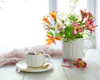 Weiße Schale mit Tee auf dem Tisch Blumen in der Nähe Lizenzfreies Stockfoto
