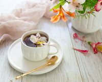 Weiße Schale mit Tee auf dem Tisch Blumen in der Nähe Lizenzfreie Stockfotografie