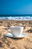 Weiße Schale mit Tee oder Kaffee auf Sandstrandfront von Meer Stockbild