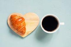 Weiße Schale schwarzer Kaffee mit frischem Hörnchen auf dem Tisch stockfotografie