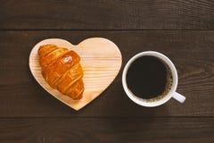 Weiße Schale schwarzer Kaffee mit frischem Hörnchen lizenzfreies stockfoto