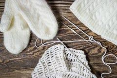 Weiße Schneeflocken auf einem blauen Hintergrund Stricken, Häkelarbeit Weiße Handschuhe und Hut Stockfoto