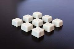 Weiße Schokolade der Süßigkeit auf einem dunklen Hintergrund Stockfotos