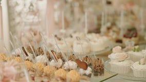 Weiße Schokoriegel-Hochzeit, Heiratsgebäck auf süßem Tabellensüßigkeitsbuffet Abschluss herauf Bewegungskamera stock footage