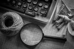 Weiße Schreibtischtabelle mit alter Schreibmaschine, Seilen, Muscheln und Lupe Draufsicht mit Kopienraum, flache Lage Stockfotografie