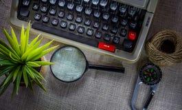 Weiße Schreibtischtabelle mit alter Schreibmaschine, Seilen, Muscheln und Lupe Draufsicht mit Kopienraum, flache Lage Stockbilder