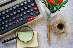 Weiße Schreibtischtabelle mit alter Schreibmaschine, Seilen, Muscheln und Lupe Draufsicht mit Kopienraum, flache Lage Lizenzfreie Stockfotos