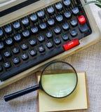 Weiße Schreibtischtabelle mit alter Schreibmaschine, Seilen, Muscheln und Lupe Draufsicht mit Kopienraum, flache Lage Lizenzfreie Stockbilder