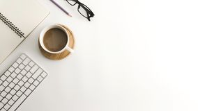 Weiße Schreibtischtabelle mit leerem Notizbuch, Computer, Versorgungen und Kaffeetasse Lizenzfreies Stockfoto