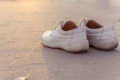 Weiße Schuhe auf dem Strand mit Weinleseart Lizenzfreies Stockbild