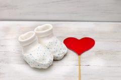 Weiße Schuhe des Beutenbabys auf einem weißen hölzernen Hintergrund und einem roten Herzen Stockbild