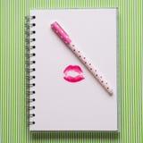 Weiße Seite mit mädchenhaftem Stift und Kuss Lizenzfreie Stockfotografie