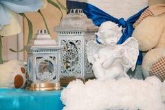 Weiße Skulptur eines Engels vor dem hintergrund der alten Lichter Stockfotos