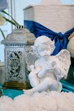 Weiße Skulptur eines Engels vor dem hintergrund der alten Lichter lizenzfreie stockfotografie