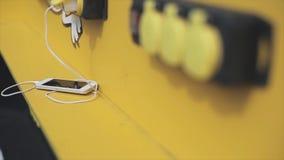 Weiße Smartphonelüge und aufgeladen auf gelber Tabelle auf Straße Sonniger Tag des Sommers telefon einheit stock video