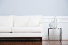 Weiße Sofa-und Glas-Enden-Tabelle gegen blaue Wand Stockfotografie