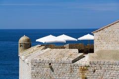 Weiße Sonnenschirme über einem blauen Meer Lizenzfreie Stockfotografie