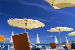 Weiße Sonnenschirme mit blauem Himmel und Wolken für Sommermeerblickkonzept Stockfotografie