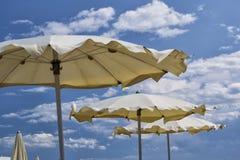 Weiße Sonnenschirme mit blauem Himmel und Wolken für Sommermeerblickkonzept Stockfotos