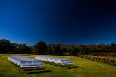 Weiße Stühle auf einem Rasen mit einem dunklen polarisierten Effekt im Himmel stockfoto